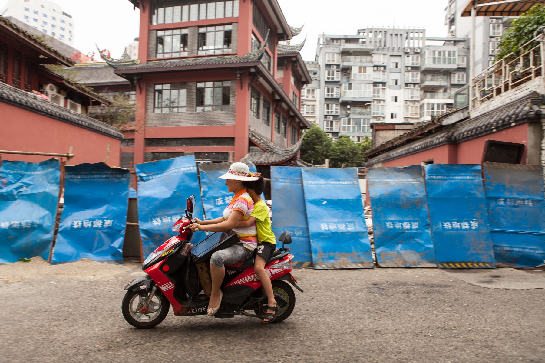 A woman in Chengdu rides a moped carrying her son and a flat-panel TV.