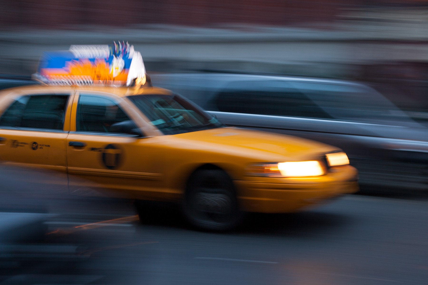 A yellow cab weaves through traffic in New York city.