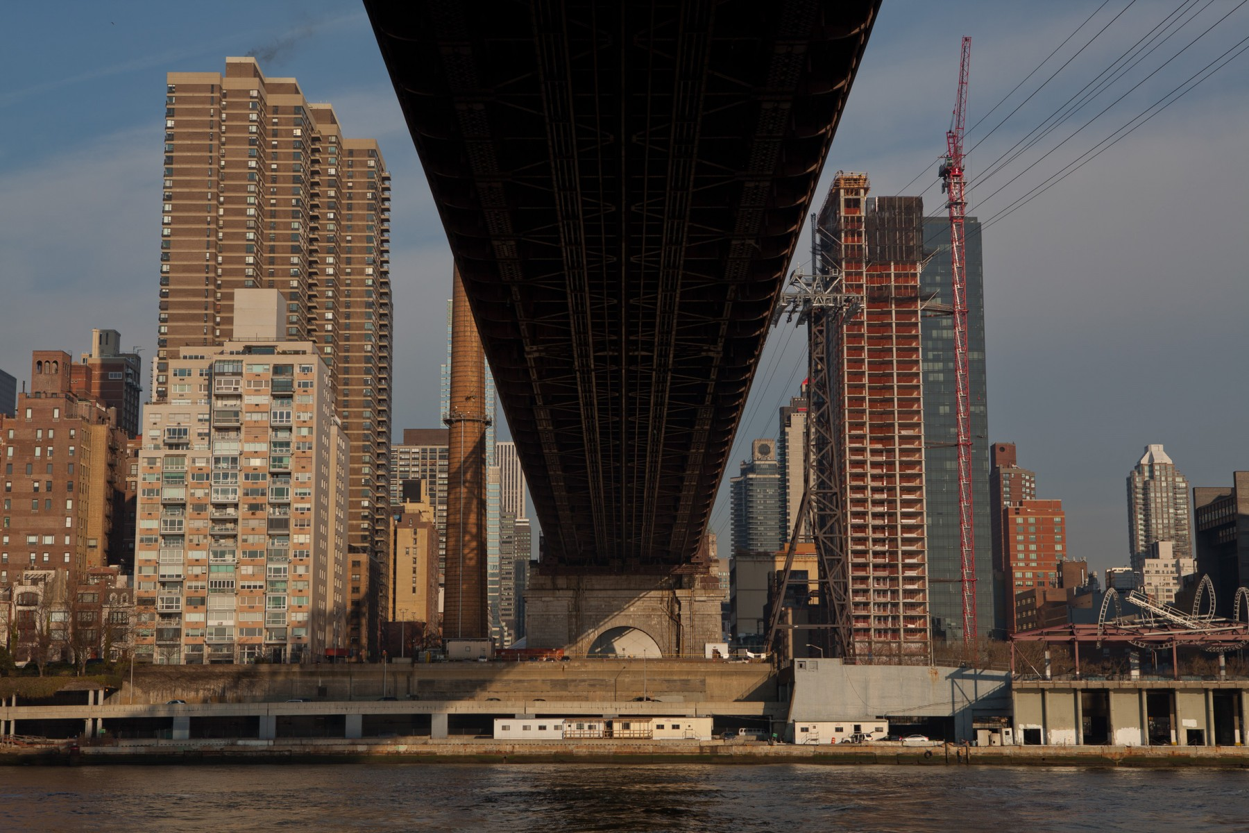 View across the East river from underneath the western span of the Queensboro Bridge.