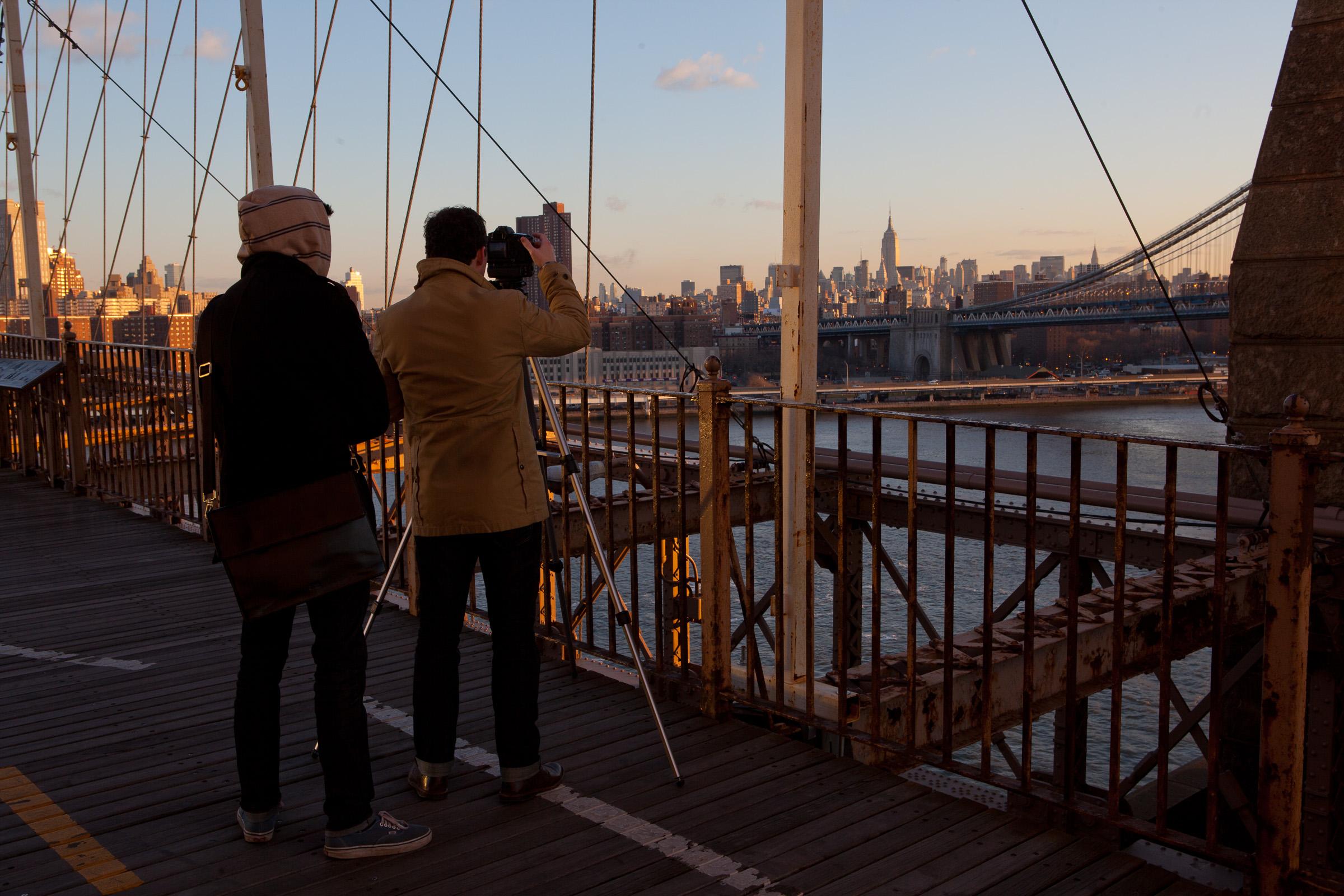 Two men shoot the sunrise from Brooklyn Bridge, NYC