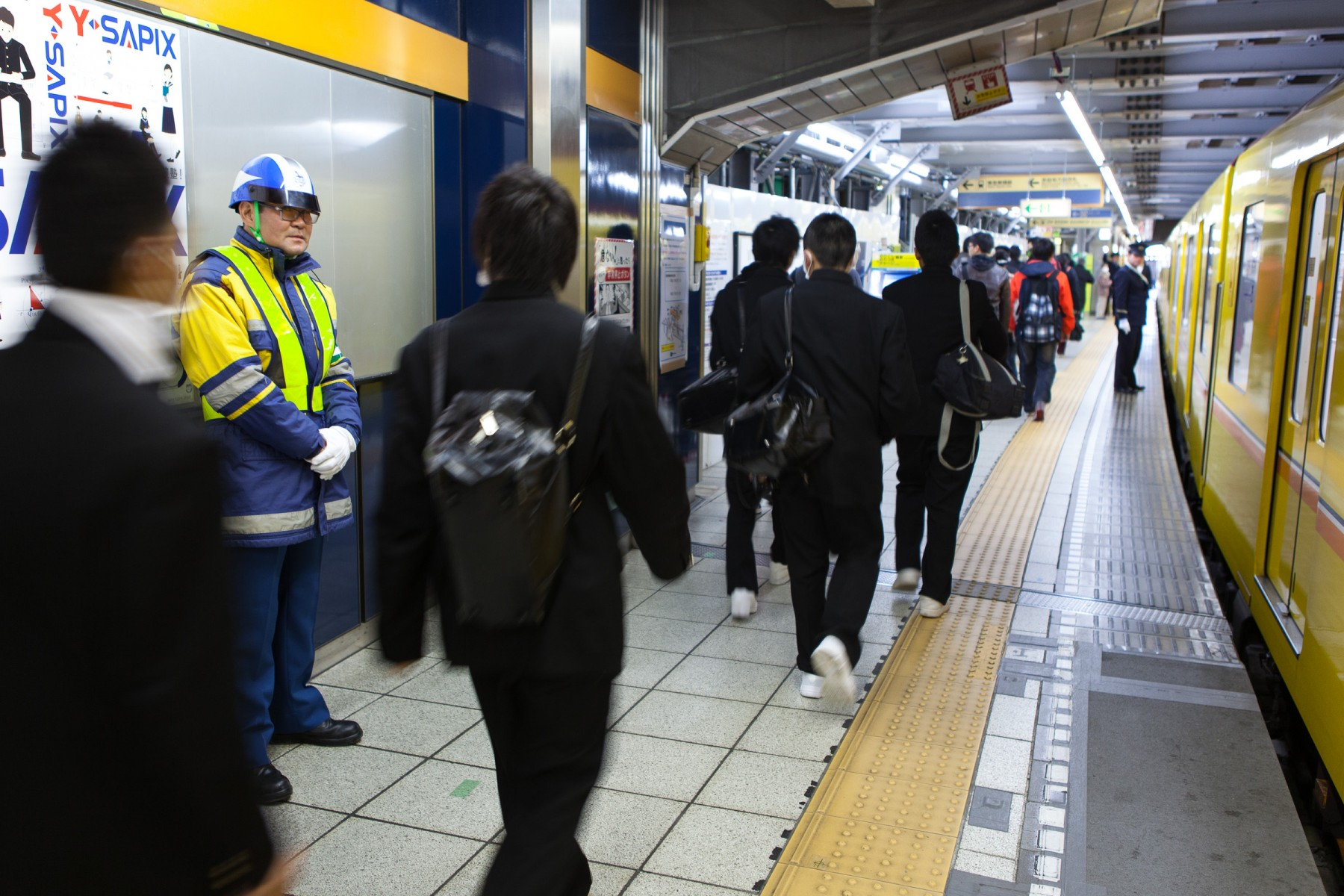Security guard keeping an eye on the platform in the Kyoto subway system.