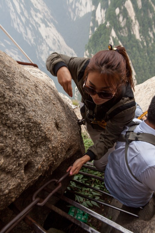 Tourists overtaking on the  plank path on the south peak of Mt Huashan