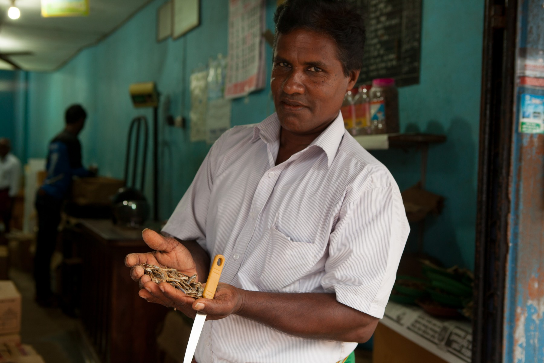 A store owner in Puttallam offering dried fish.