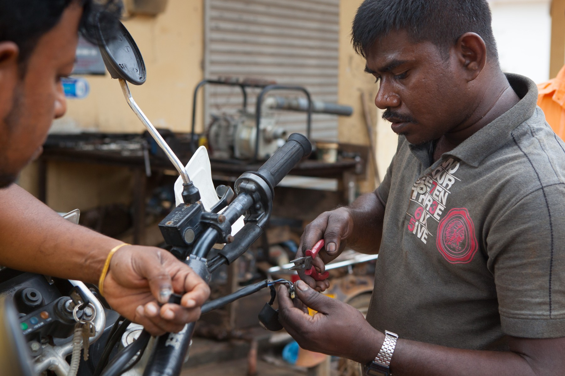 The mechanic in Wanathavilluwa works on the electric starter on Ryan's bike.
