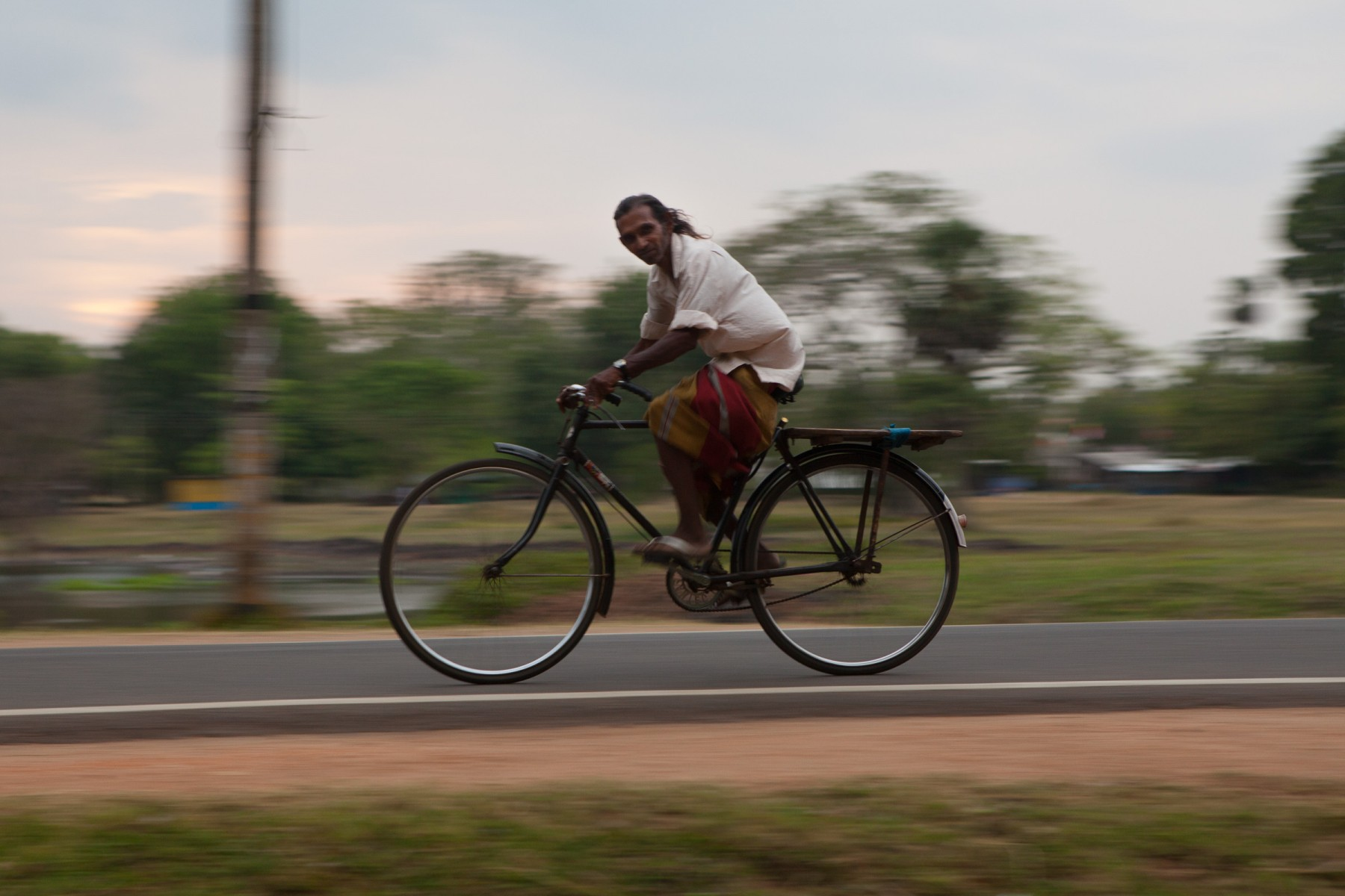 Man cycling at dusk near the Sangamiththa Stupa.