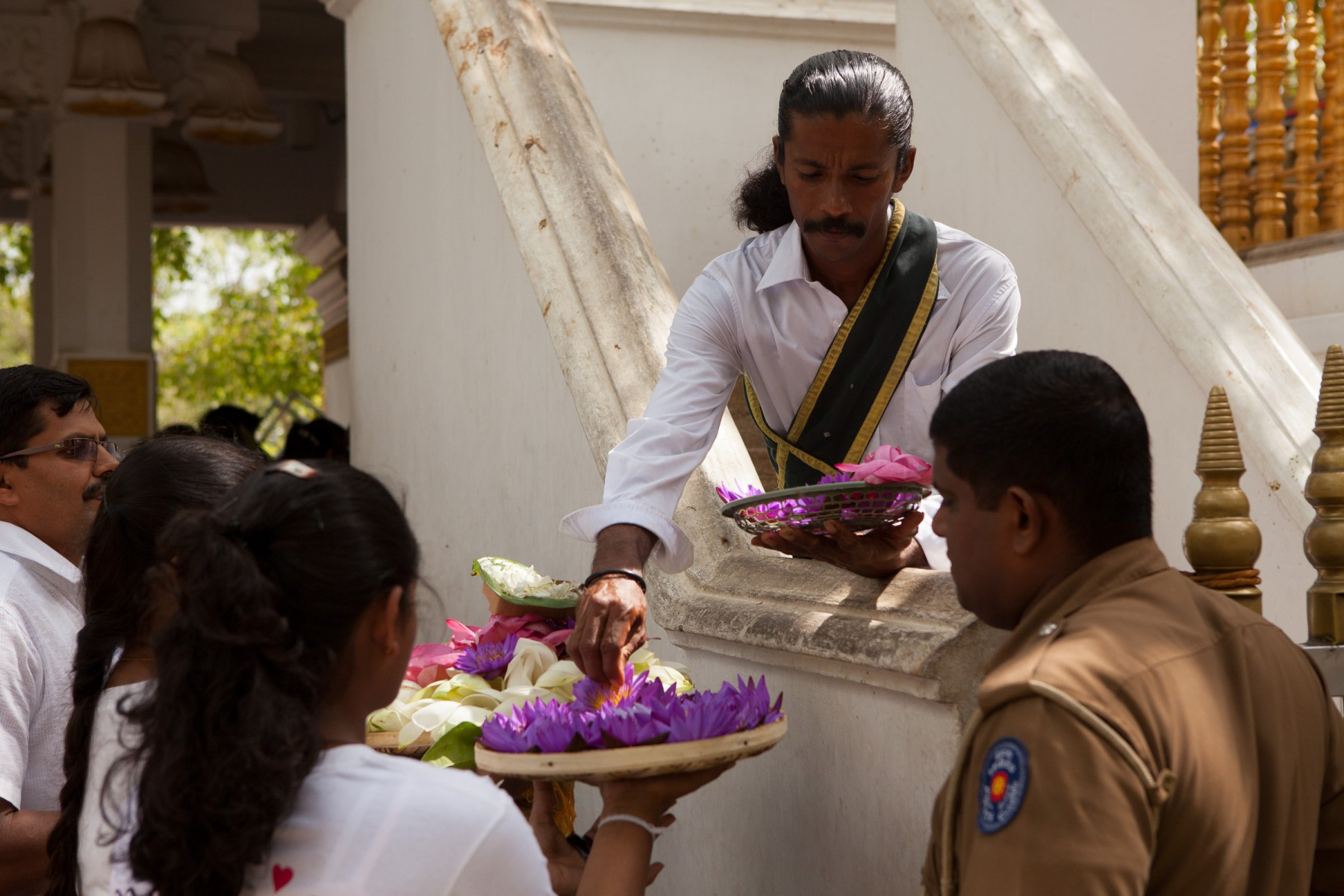 Offerings being made to an attendant at the Jaya Sri Maha Bodhi.  The tree at the temple is said to have been grown from a cutting of the Bodhi tree under which Budda achieved enlightenment. It was brought to Sri Lanka by the Theri Sangamitta, daughter of Emperor Asoka in 249 BC making it possibly the oldest tree planted by humans.