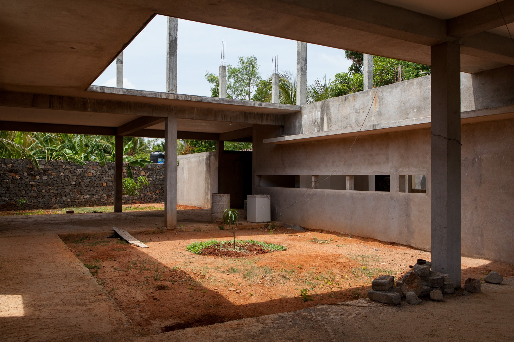 A palm tree sapling planted in the middle of an atrium in a construction site just outside Anuradhapura.