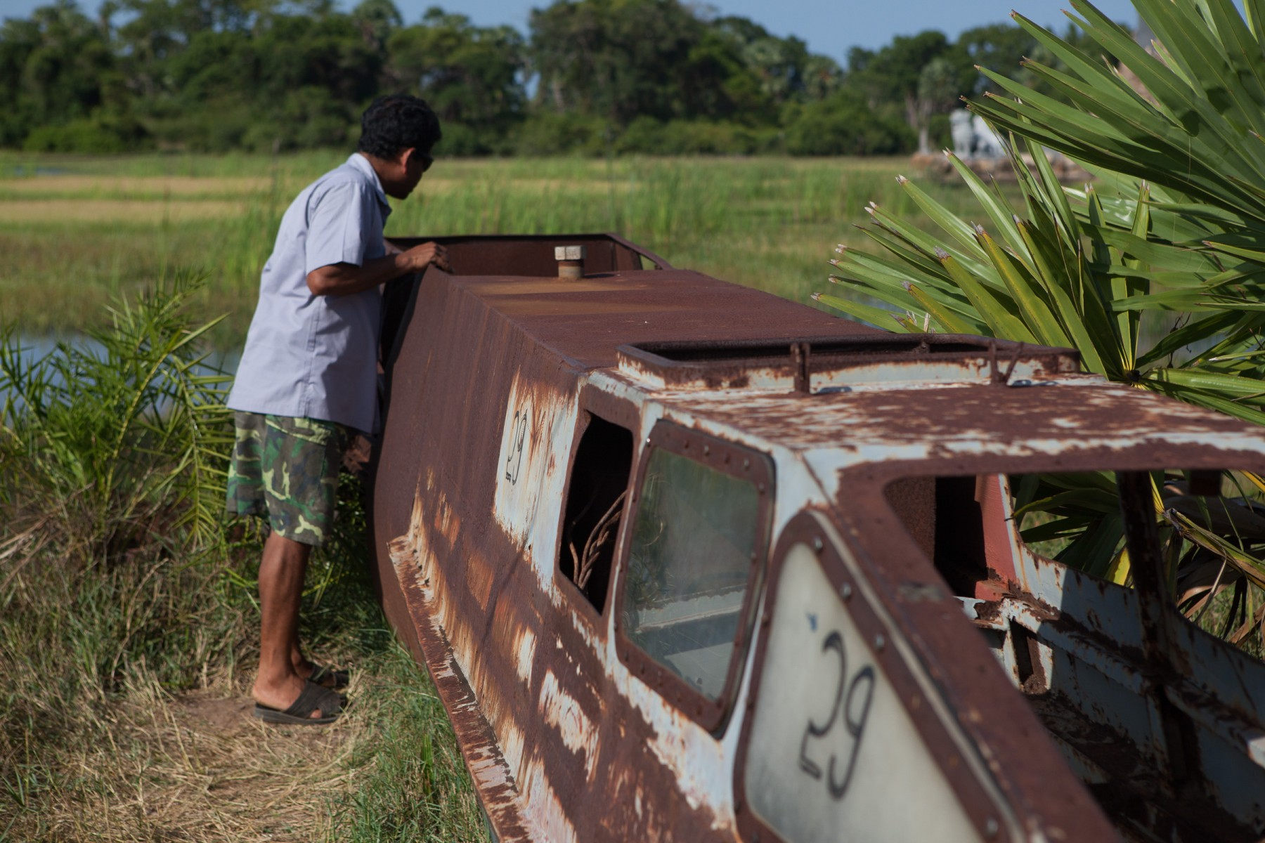 A man inspects the rusted remains of an LTTE submersible.