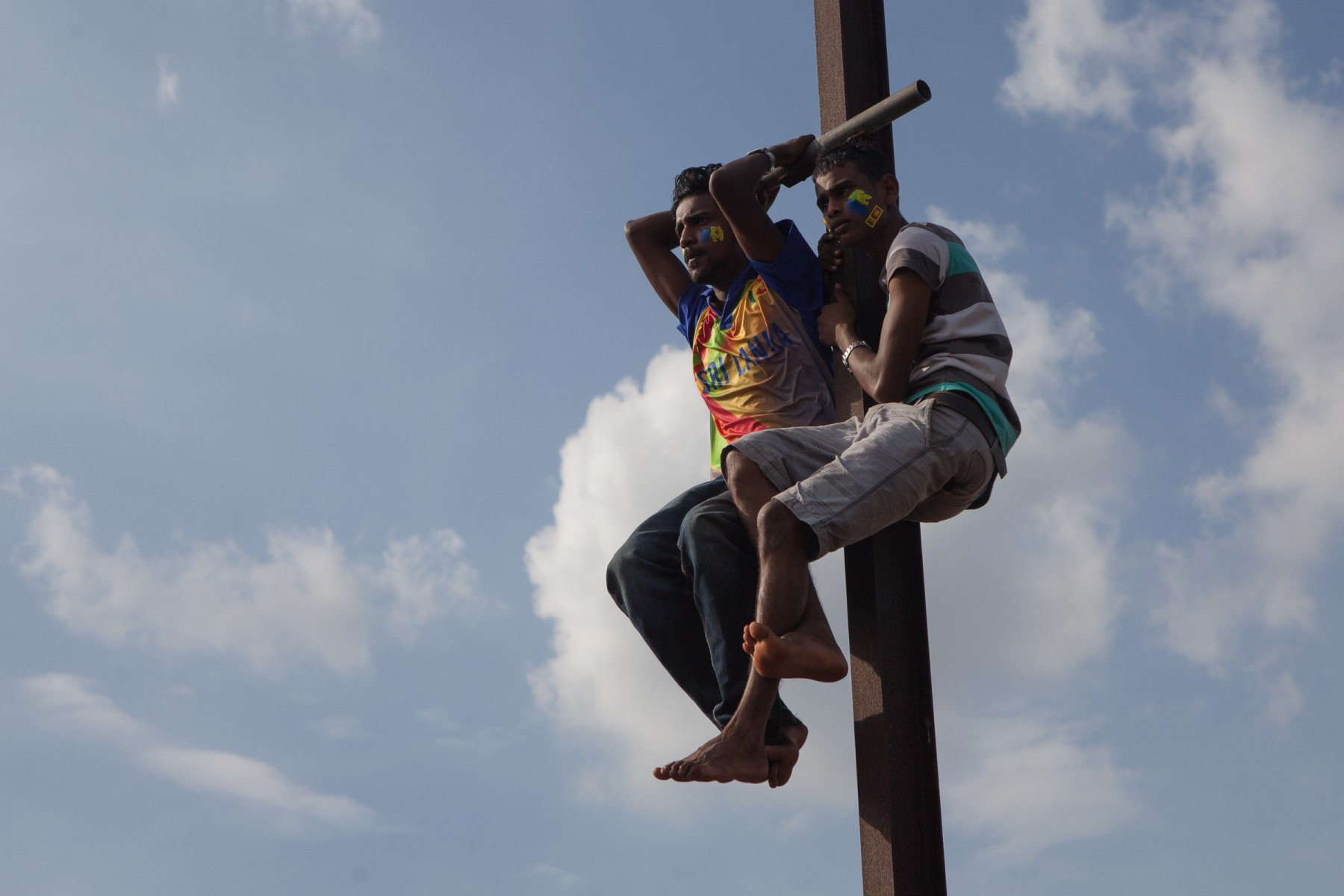 Sri Lankan cricket fans perched on a post at Rangiri Dambulla International Stadium.