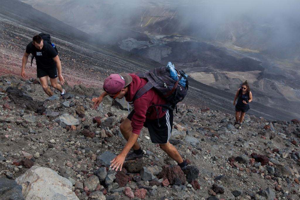 Hikers close to the summit of Mount Ngauruhoe.  The climb is steep with deep scree most of the way but small ridges of hardened rock at the top make the climb easier.