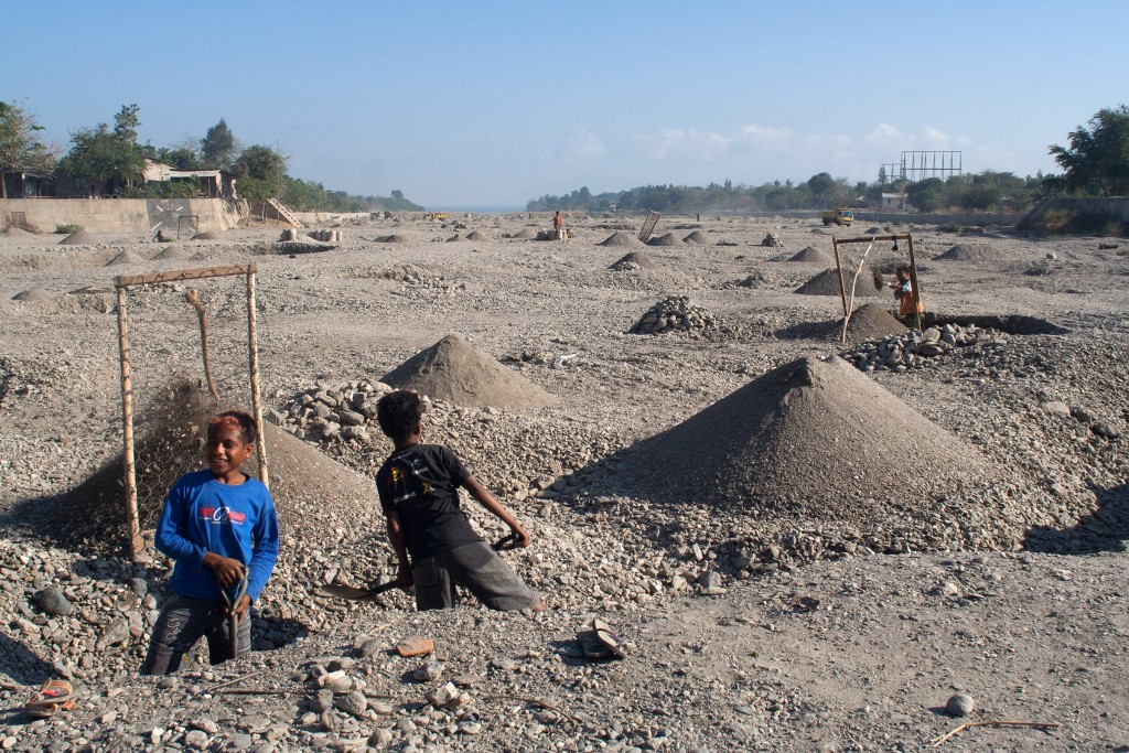 Children digging gravel for concrete in the bed of the Comoro River in Dili during the dry season.