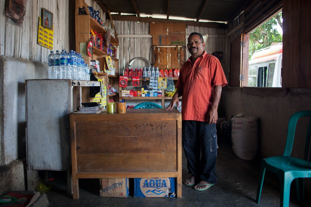 Shopkeeper on the road back from Cova Lima district.  Essentials include water, fuses, motor oil and sprockets.