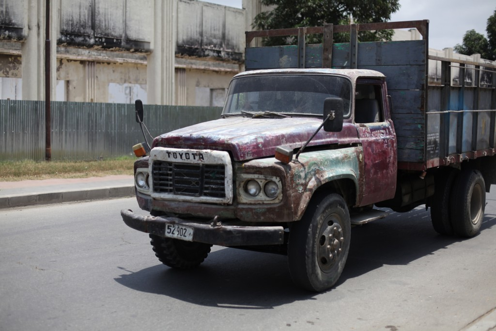 Rough looking Toyota truck outside a burned out building in Dili, East timor.