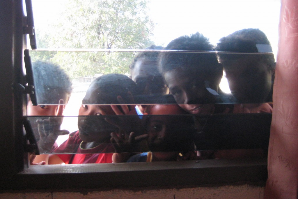 Kids crowding the window of the youth centre in Zumalai